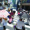 People carrying parasols walk across a pedestrian crossing in Tokyo on Friday.
