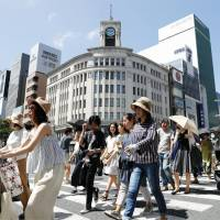People are seen walking in Tokyo's Ginza district on Sunday. The number of people taken to hospital due to heatstroke surged in the week to Sunday. | KYODO