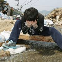 A volunteer worker washes his face at a stream Wednesday while clearing up the disaster-hit city of Kure, Hiroshima Prefecture. | KYODO