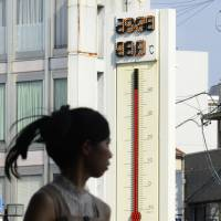 A woman walks past a thermometer display showing 41.3 degrees Celsius in front of Tajimi Station in Gifu Prefecture on Wednesday afternoon. | KYODO