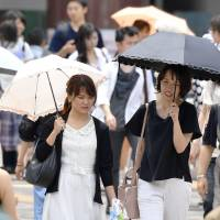 Women holding parasols walk under the scorching sun in the city of Saitama on Sunday. | KYODO