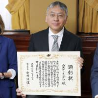 Kazuo Ishiguro and his wife Lorna pose for a photo in London on Tuesday after the Nobel Prize-winning author received honorary citizenship certificates from the Nagasaki prefectural and city governments.   KYODO