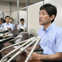 Fumihiro Joyu, head of Hikari no Wa (The Circle of Rainbow Light), an Aum Shinrikyo splinter group, is seen at a news conference in Tokyo on Friday following the executions earlier in the day of seven cultists, including Aum founder Shoko Asahara.   KYODO