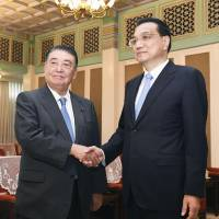 Lower House Speaker Tadamori Oshima (left) greets Chinese Premier Li Keqiang on July 24 during his visit to Beijing. | KYODO