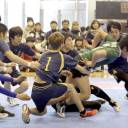 Members of the Jiyunomori Gakuen Junior and Senior High School kabaddi club tackle a raider (right) during the 2018 national student championship in Tokyo in February.