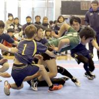 Members of the Jiyunomori Gakuen Junior and Senior High School kabaddi club tackle a raider (right) during the 2018 national student championship in Tokyo in February. | KYODO
