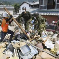 Self-Defense Forces personnel clear piles of debris in Hiroshima on Wednesday. | KYODO