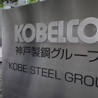 Signage for Kobe Steel stands outside the company's offices in Tokyo in May. The company is expected to be indicted over its data fabrication. | BLOOMBERG