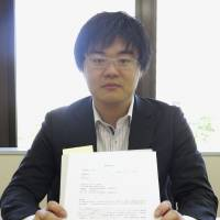 Kenta Ikeda, one of a number of lawyers targeted by a Japanese blog, holds a document that urges he be punished for expressing support for subsidizing Korean schools with ties to North Korea in this photo taken May 30 in Sapporo. | KYODO