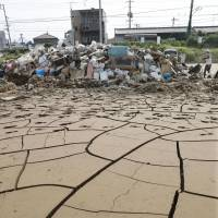 Mud from torrential rain this month is now dry and cracking in Kure, Hiroshima Prefecture, while a pile of debris awaits disposal. | KYODO