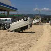 A car rests on its roof after floodwaters receded in the Mabicho district of Kurashiki, Okayama Prefecture, on Tuesday. | ERIC JOHNSTON
