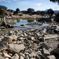 Houses that have been badly damaged or destroyed are seen on July 9 near the site where the banks of the Suemasa River in the Mabicho district of Kurashiki, Okayama Prefecture, broke. | REUTERS
