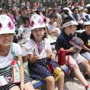 Children attend an event for the 2020 Tokyo Olympic mascot unveiling in Tokyo's Hibiya district Sunday.