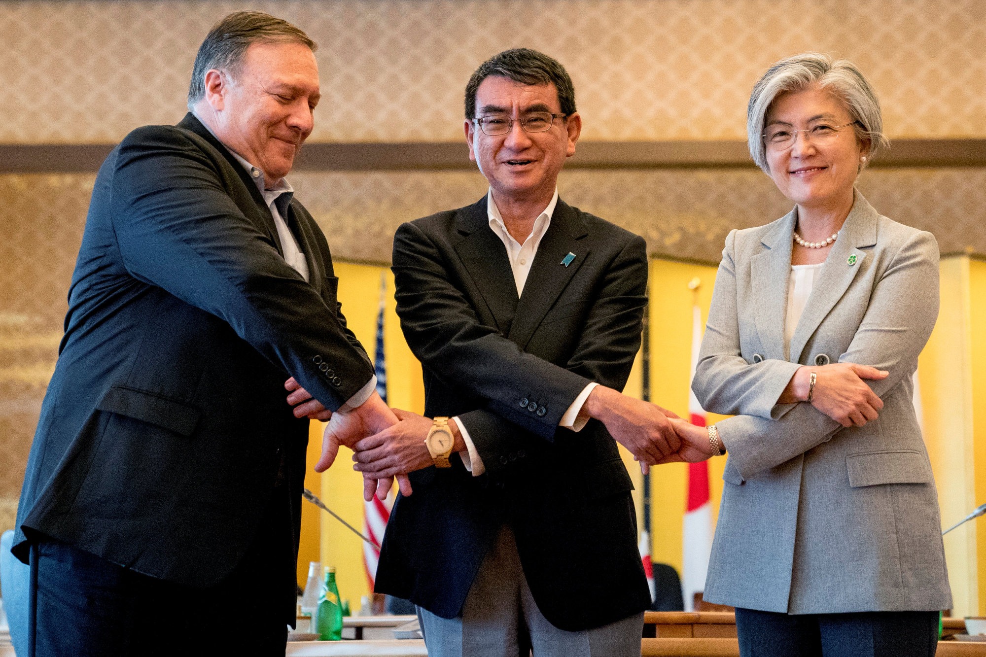 U.S. Secretary of State Mike Pompeo, Japan's Foreign Minister Taro Kono and South Korea's Foreign Minister Kang Kyung-wha shake hands for members of the media as they meet in Tokyo on Sunday.   REUTERS