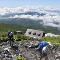 Climbers walk on Mount Fuji's Fujinomiya trail in Shizuoka Prefecture on Tuesday, as the climbing season begins in the prefecture for the 3,776-meter volcano. | KYODO