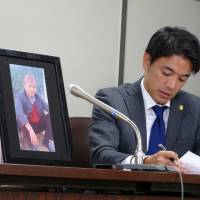 A photo of Arjun Bahadur Singh, a Nepalese man who died last year while being interrogated by prosecutors, is displayed at a news conference Friday in Tokyo next to lawyer Yoshihito Kawakami. | SAKURA MURAKAMI