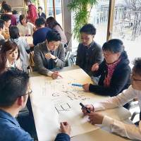 Participants meet to discuss nursing care for the elderly at a Kaigo Cafe event in Hakusan, Ishikawa Prefecture, in March. | HISAKO TAKASE / VIA KYODO