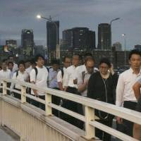 Pedestrians crowd the Shin-Yodogawa Bridge in Osaka on the evening of June 18 after public transportation services were disrupted by the major earthquake that hit the region earlier in the day. | KYODO