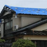 As heavy rain falls in Takatsuki, Osaka Prefecture, on Thursday, a house roof is seen covered with a blue plastic sheet. | KYODO