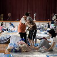 An elderly woman is given assistance as people affected by the recent flooding rest at a makeshift shelter at a gymnasium in the Mabicho district of Kurashiki, Okayama Prefecture, on Wednesday.   AFP-JIJI
