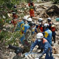 Rescuers and Self-Defense Forces personnel remove debris Friday in Aki Ward in the city of Hiroshima. | KYODO