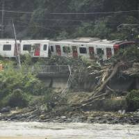An emergency crew works on a section of the Chikuhi Line, operated by JR Kyushu, where a train derailed after landslides on Saturday in Karatsu, Saga Prefecture.