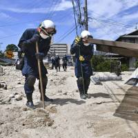 Rescuers search for missing people near houses and cars buried in mud in Kure, Hiroshima Prefecture, on Wednesday.   KYODO