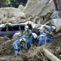 Rescuers continue to search for people missing at a site in the town of Kumano, Hiroshima Prefecture, on Tuesday after heavy rains over the weekend prompted widespread flooding and mudslides.   KYODO