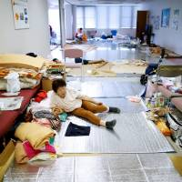 An evacuee takes a rest at the Mabi Clean Center, which is acting as an evacuation site, in Kurashiki, Okayama Prefecture, on Friday. | REUTERS