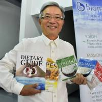 Kiyosada Egawa, president of Biotech Japan Corp., presents precooked, ready-to-eat rice products sold by the firm's Philippines subsidiary near Manila in June. | KYODO