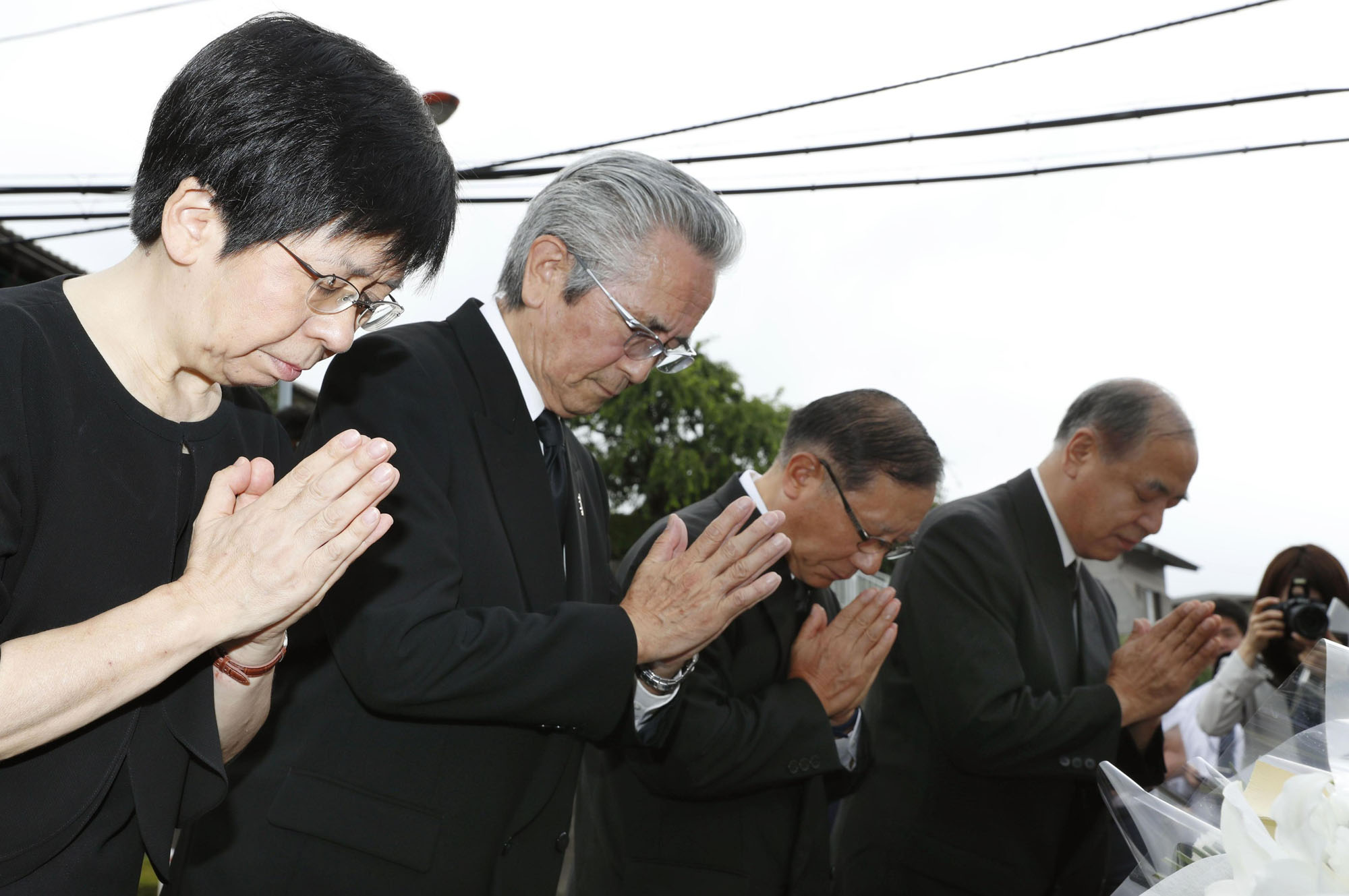 Kaoru Irikura (far left), head of the care home Tsukui Yamayuri En in Sagamihara, Kanagawa Prefecture, offers a prayer in front of the facility on Thursday, the two-year anniversary of a fatal stabbing rampage that took place there. | KYODO