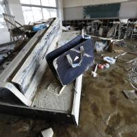 An overturned piano remains caked in mud in a junior high school classroom in the Mabicho district of Kurashiki, Okayama Prefecture, after floodwaters inundated the area more than a week ago. | KYODO