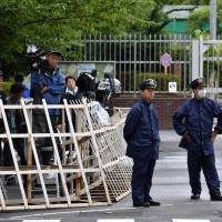 Police stand guard near the gate of the Tokyo Detention House in Adachi Ward where Aum Shinrikyo founder Shoko Asahara was executed on Friday. | SATOKO KAWASAKI