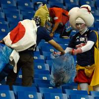 Japan supporters collect garbage after the 2018 World Cup round of 16 soccer match between Belgium and Japan at the Rostov Arena in Rostov-On-Don, Russia, on Monday. | AFP-JIJI