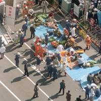 Victims of the sarin gas attack in the Tokyo subway system by members of the Aum Shinrikyo cult receive treatment on the street in front of Tsukiji Station on March 20, 1995. | KYODO