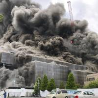 A photo provided by a person involved in the construction work shows massive black smoke filling a building site in Tama, Tokyo, around 2 p.m. Thursday.   KYODO