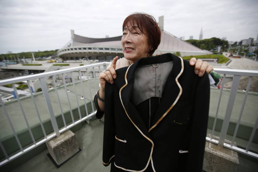 Interpreter Mariko Nagai holds a jacket in May that she wore during the 1964 Tokyo Olympics. Behind her is Yoyogi National Gymnasium.  AP | AP