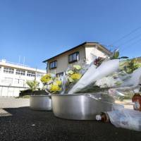 Flowers and drinks are laid out at the entrance of Okuda Elementary School in the city of Toyama on Monday while the school remains closed. | KYODO
