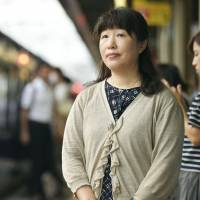 Hikaru Nagano stands on a train platform at Ashiya Station in Hyogo Prefecture on July 4. Nagano volunteered to make an English-language announcement for foreign visitors on a train that was halted by the Osaka earthquake on June 18. | KYODO
