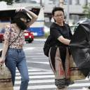 Women are buffeted by strong winds in Nagoya on Saturday afternoon as Typhoon Jongdari approached western Japan.