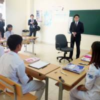 Foreign Minister Fumio Kishida (second from right at the back) talks with Vietnamese students in a Tokyo-funded Japanese language course during his visit to Hanoi in July 2014. The students hope to work in Japan as care workers. | KYODO