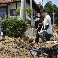 Volunteers attempt to remove debris in Higashihiroshima, Hiroshima Prefecture, on Saturday. | KYODO.