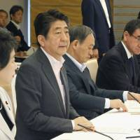 Prime Minister Shinzo Abe speaks during a ministerial meeting on Tuesday about the government's plan to accept more foreign workers from April. | KYODO