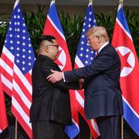 North Korean leader Kim Jong Un shakes hands with U.S. President Donald Trump at the start of their summit in Singapore in June. | GETTY IMAGES / VIA KYODO