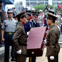 North Korean soldiers hand over a casket containing the remains of a U.S. serviceman who served in the Korean War in July 1993. | REUTERS