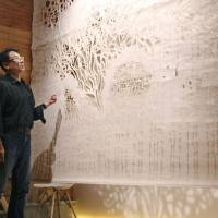 'Washi sommelier' Yoshinao Sugihara, the 10th-generation successor of an Echizen paper wholesaler presents a washi tapestry on display at his gallery. | KYODO