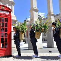 Messengers deliver blooms selected by flower artist Makoto Azuma to members of the public for the opening of Japan House London. | JAPAN HOUSE LONDON