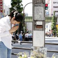 A woman prays near the site of a 2008 stabbing rampage in Tokyo's Akihabara district on June 8, 2018, the 10th anniversary of the incident that killed seven people and injured 10 others.   KYODO