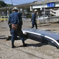 Police officers inspect a car buried in mud on July 11 after heavy rain in Kure, Hiroshima Prefecture. | KYODO