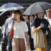 Women walk with parasols amid a continued heat wave in Tokyo on July 23. | KYODO